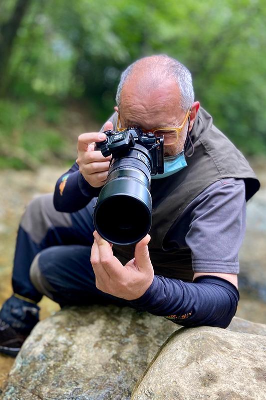 Fotografo con macchina fotografica in mano durante un workshop di fotografia naturalistica personalizzato.